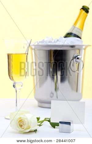 Photo of a white rose on a table with white tablecloth and a glass of champagne plus bottle in an ice bucket in the background. Blank place card to add your own message.