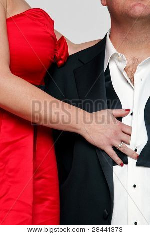 Photo of a woman in a red dress with red fingernails unbuttoning the shirt of a man wearing a tuxedo and black tie.