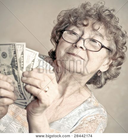Portrait of happy elderly woman checking dollars money