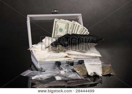 ?ocaine and marijuana with gun in a suitcase on grey background