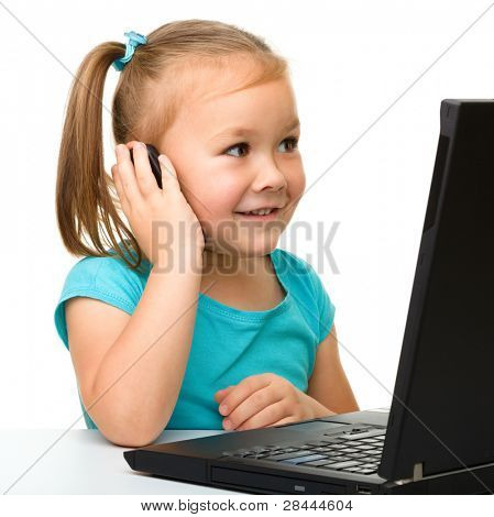 Cute little girl is sitting at table with her black laptop and talking to a cell phone, isolated over white