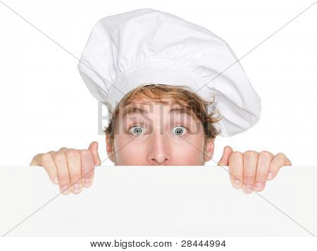 Chef sign. Man chef, cook or baker peeking up holding blank white paper sign with copy space for text or menu. Young Caucasian male chef looking funny surprised isolated on white background.