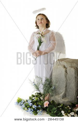 "An elementary ""angel"" looking heavenward while holding an Easter lily and standing by a boulder surrounded by spring flowers.  On a white background."