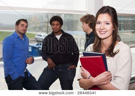 Retrato de joven, mujer, estudiante, sostiene un par de libros con un grupo de chicos que se inclinan en el