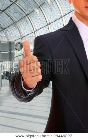 A handsome young business man thumb up at office building