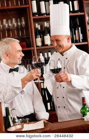 Chef cook and waiter toasting with wine smiling in restaurant