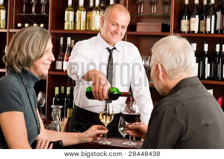 Wine bar senior couple enjoy drink professional barman pour glass