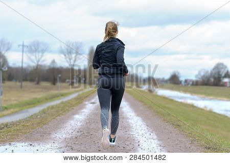 Fit Muscular Woman Jogging Away