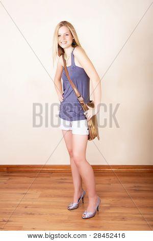 Longitud total de una encantadora joven sonriendo con largos cabellos rubios y sosteniendo una bolsa grande del estudiante
