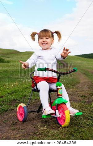 Laughing little girl riding a bicycle