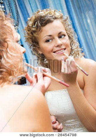 pretty smiling bride near the mirror