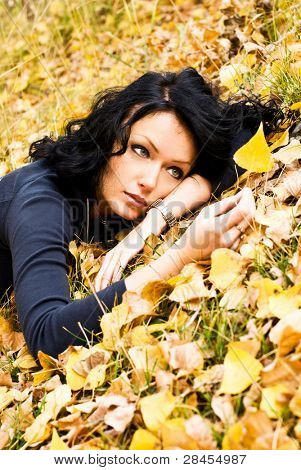 girl disappointed with the end of the summer lies on the grass and looks at the yellow leaf