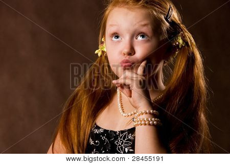 cute capricious little girl against brown background