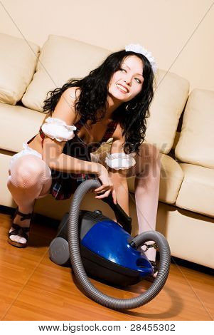 sexy beautiful brunette maid with the vacuum cleaner has a break