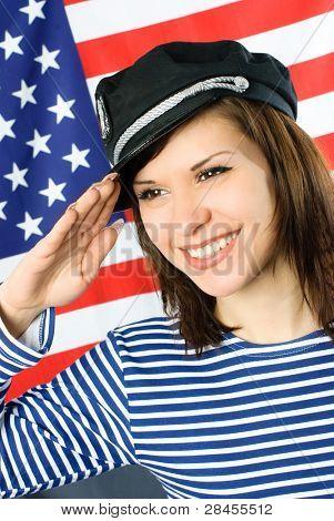 glücklich schöne junge Segler steht in der Nähe der amerikanischen Flagge und begrüßt