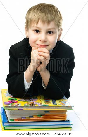 little schoolboy sitting by the table with a lot of books standing on it