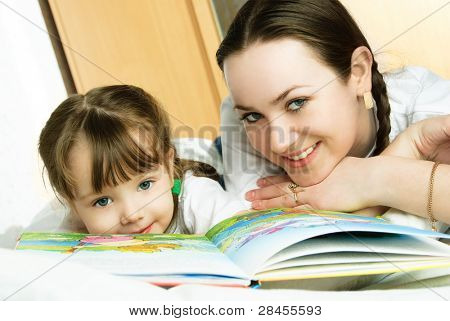 young beautiful mother and her little daughter lie on the bed and read a book