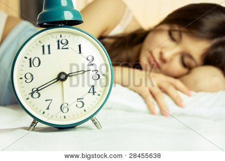beautiful young brunette woman sleeping peacefully in bed with the alarm clock standing near her