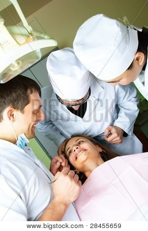 drei Zahnärzte bücken der Patient und überprüfen Sie ihre Zähne