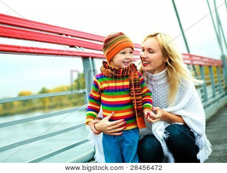 young mother with her little son outdoor on the bridge