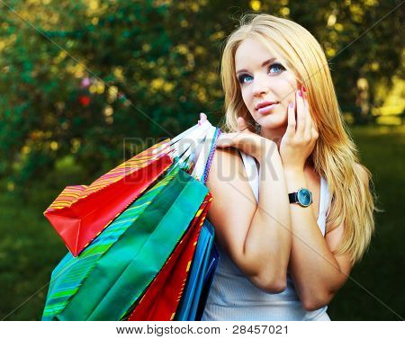 pretty blond woman with many small shopping bags