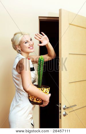 beautiful young businesswoman with a flower in her hands leaving the job