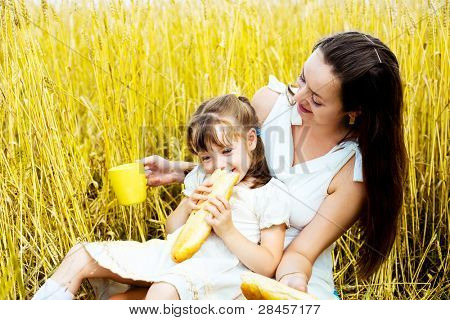 happy mother and her  little daughter having a picnic  in the wheat field