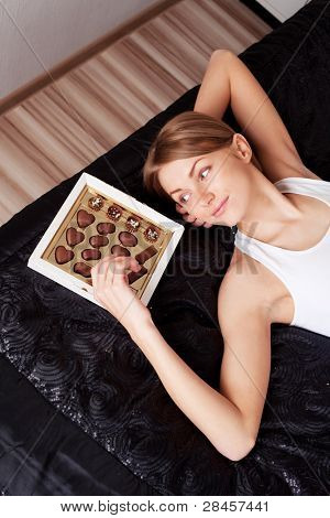 pretty young woman eating candies at home on the bed