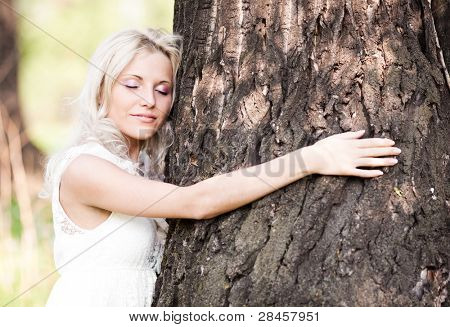 beautiful young blond woman embracing a big tree  on a warm summer day