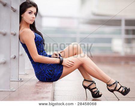 schöne junge Brünette Frau trägt ein blaues Kleid auf der Straße