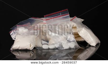 Cocaine and drugs in packages on black background