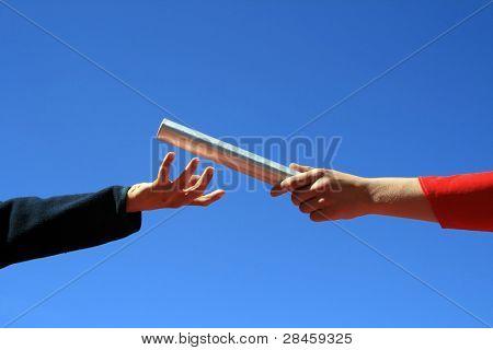 hands passing the batton against blue sky