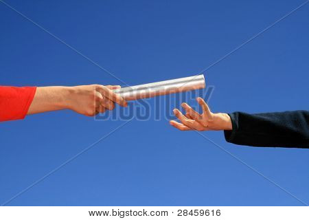 hands passing the batton against blue sky