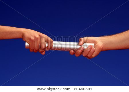 hands passing the baton against blue sky