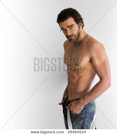 portrait of a sexy muscular shirtless man against neutral background with copy space