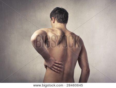 Vista posterior de un joven que sufre de dolor de espalda