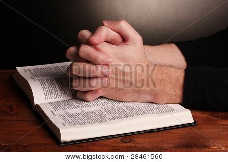 Hands folded in prayer over a Holy bible on wooden table on grey background