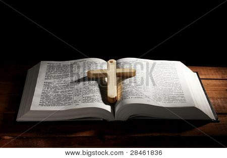 Russian open holy bible with wooden cross on table