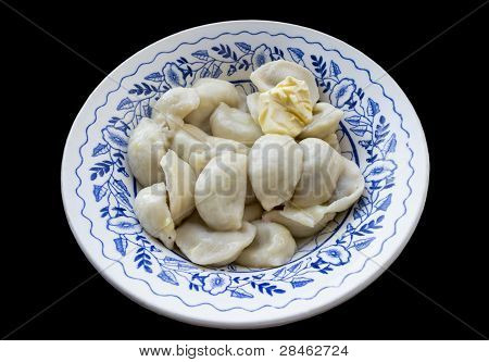 The Blue Patterned Plate Full Of Dumplings, Seasoned With A Piece Of Butter. Isolated On A Black Bac