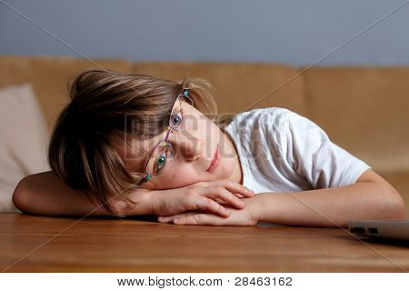 Young sad and tired schoolboy in glasses, almost sleeps on his desk