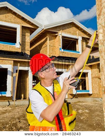A man in a hard hat standing in front of an house over blue sky with white clouds at sunny day holding a measure tape in his hand.