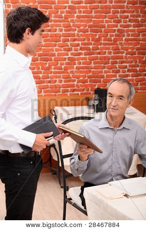 Waiter proposing menu to client