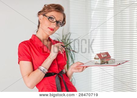 Businesswoman With A Model Of House.
