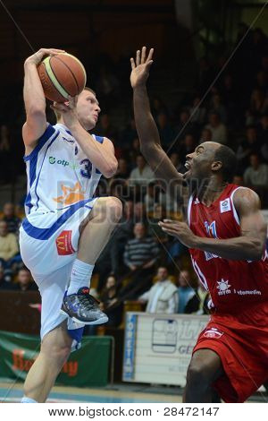 KAPOSVAR, HUNGARY - NOVEMBER 19: Nik Raivio (white 33) in action at a Hugarian National Championship  basketball game Kaposvar (white) vs. Paks (red) November 19, 2011 in Kaposvar, Hungary.