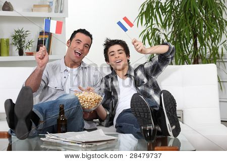 two guys watching football on the couch