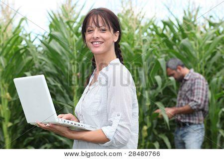 Mujer con su ordenador portátil en un campo de cultivos