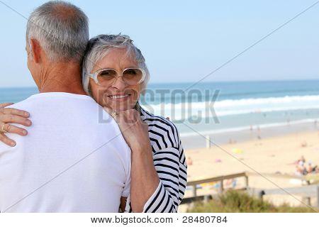 a senior woman hugging her husband near the sea