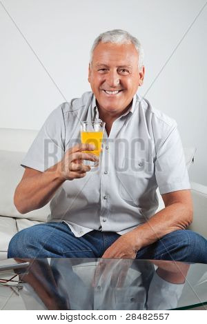 Portrait of happy senior man having glass of fresh orange juice