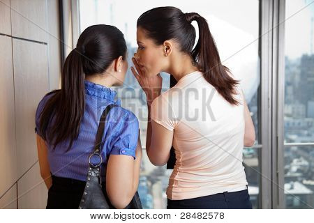 Two female co-workers whispering in office