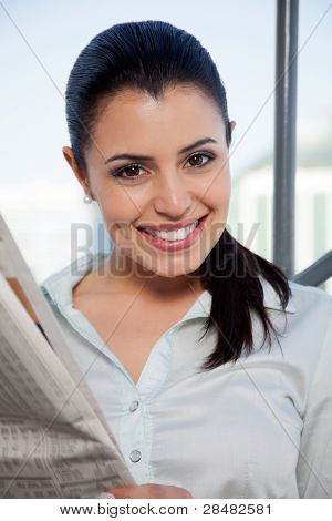 Portrait of happy female executive holding newspaper